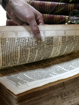 Gene S. Albert Jr. opens a first edition King James Bible, its ornate letters and decorations still clearly legible after 395 years, at his Christian Heritage Museum on July 18, 2006, in Hagerstown, Maryland.